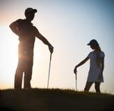 日落的男性和女性高尔夫球运动员 免版税库存照片