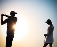 日落的男性和女性高尔夫球运动员 库存照片
