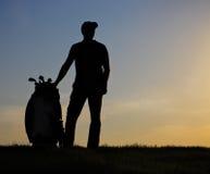 日落的男性高尔夫球运动员 库存图片