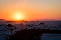 日落的米科诺斯岛镇与巡航划线员在背景中 库存照片