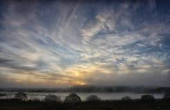 日落的美好的风景在湖的雾的 免版税库存图片