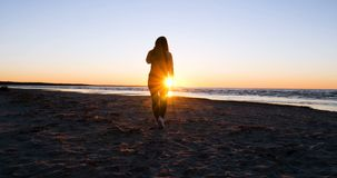 日落的背景的妇女在海滨的太阳锻炼 股票录像