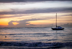 日落的阿鲁巴沿海图象与小船的在背景中 库存图片