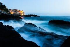 日落的风雨如磐的海与教会 免版税库存照片