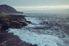 日落的风暴海在山海岸 免版税库存照片