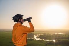 日落的骑自行车者在山 盔甲和玻璃的一个年轻人喝从瓶的水 图库摄影