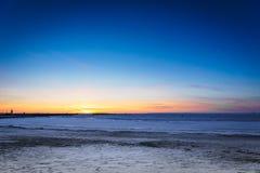 日落的-在海滩的波罗的海日落冻海洋在塔林,爱沙尼亚 免版税图库摄影