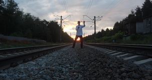 日落的Gentalman变戏法者在铁路做把戏 股票录像