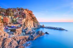 日落的Manarola村庄、岩石和海运。 Cinque Terre,意大利 免版税库存照片