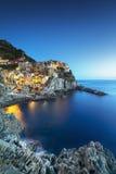 日落的Manarola村庄、岩石和海运 Cinque Terre,意大利 免版税库存图片