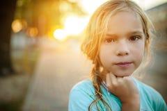 日落背景的小女孩在街道上的 库存照片