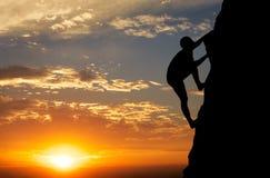 日落背景的攀岩运动员 免版税库存图片