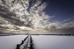 日落被观看的形式的冻湖码头。 免版税图库摄影