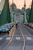 日落观点的汽车和骑自行车者自由桥梁的在日落在布达佩斯匈牙利 图库摄影