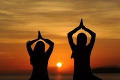 日落视图的瑜伽妇女 免版税库存图片