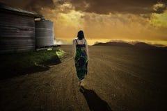 日落走的妇女 免版税库存图片