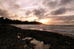 日落通过云彩和反射在作为他们的波浪增殖比 免版税库存图片