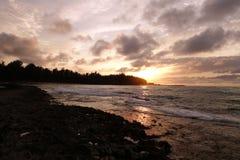 日落通过云彩和反射在作为他们的波浪增殖比 免版税库存照片