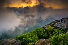 日落通过雾,看见从崎岖的石峰,在被赶走的蓝色附近 免版税图库摄影