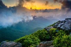 日落通过雾,看见从崎岖的石峰,在被赶走的蓝色附近 免版税库存照片