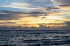 日落阴云密布天空,橙色光,风平浪静波浪 免版税库存图片