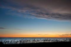 日落颜色在日落以后的微明下沿海滩 免版税库存照片