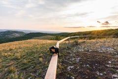 日落风景全景、小山在金黄小时,谷的小村庄,美好的颜色和云彩 图库摄影