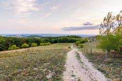 日落风景全景、小山在金黄小时,谷的小村庄,美好的颜色和云彩 免版税库存图片