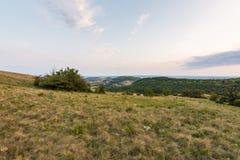 日落风景全景、小山在金黄小时,谷的小村庄,美好的颜色和云彩 免版税图库摄影