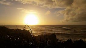 日落风雨如磐的波浪岩石海岸 库存照片