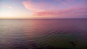 日落鸟瞰图在海洋的 天空、云彩和wa 免版税库存图片