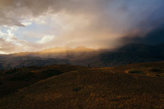日落,在一朵多灰尘的云彩的明亮的阳光,在山谷的旅行,风景 图库摄影