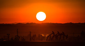 日落,在前面的petro提取器 免版税库存照片
