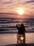 日落,在海滩做观光轮椅的一名妇女 免版税库存图片