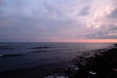 日落,太阳` s光芒通过重的云彩做他们的方式并且阐明夏天,混乱的海 图库摄影