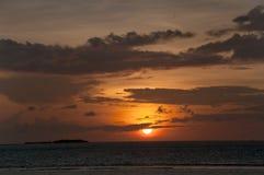 日落,火球接近天际,照亮在橙色和红色口气的天空,马尔代夫,印度洋 免版税库存图片