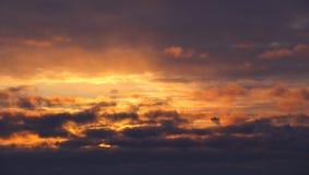 日落 在密集的黑暗的云彩的晚上冬天天空 太阳通过冷淡的空气和云彩发光明亮的黄色温暖的光在 免版税库存照片