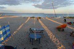 日落从海滩小屋的阴影塑象往岸和美丽的天空 免版税库存照片