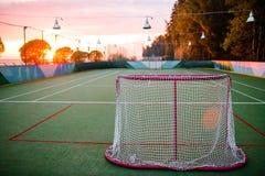 日落 绿草海的银行的橄榄球操场 图库摄影