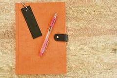 日记本和笔在木桌上 免版税图库摄影