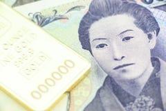 日语五千日元票据,与金锭的一个宏观特写镜头 库存图片