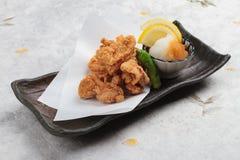 日语油炸了与烹调纸的Karaage服务与天麸罗调味汁Tentsuyu混合剁碎萝卜的鸡 库存照片