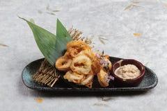 日语油炸了乌贼混合的天麸罗面粉乌贼Karaage服务用在黑色的盘子washi日文报纸的调味汁 免版税库存图片