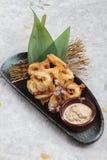 日语油炸了乌贼混合的天麸罗面粉乌贼Karaage服务用在黑色的盘子washi日文报纸的调味汁 图库摄影