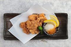 日语顶视图油炸了与烹调纸的Karaage服务与天麸罗调味汁Tentsuyu混合剁碎萝卜的鸡 免版税库存照片