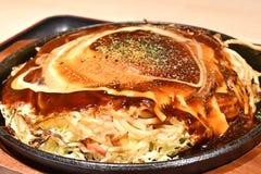 日语Modanyaki,一个美味薄煎饼用油煎的面条填装了 免版税库存照片
