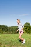 日跑步的草甸嬉戏晴朗的妇女年轻人 免版税库存照片