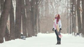 日霜1月天然公园多雪的结构树冬天 大雪 有明亮的红色头发身分的一名妇女在边路 与嘴的捉住的雪花 股票录像