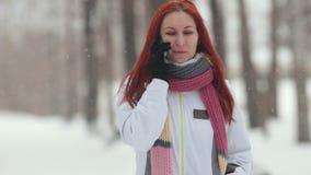 日霜1月天然公园多雪的结构树冬天 有明亮的红色头发的一名妇女谈话在电话 大雪 关闭 股票录像