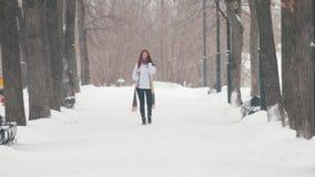 日霜1月天然公园多雪的结构树冬天 有明亮的红色头发的一名妇女谈话在电话 大雪 恶劣天气 股票录像